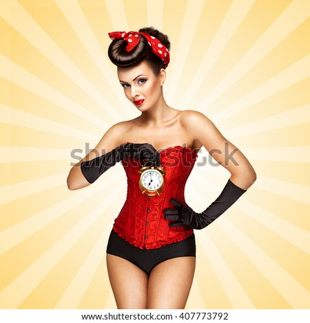 Glamorous pinup girl in a red vintage corset holding a retro alarm clock in her hand and posing on colorful abstract cartoon style background. - stock photo
