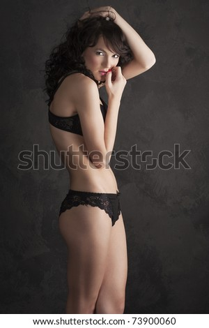 Glamorous sexy standing woman in black lingerie on black background - stock photo