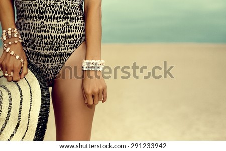Glamorous tanned Model in  fashionable Swimsuit and stylish Accessories at the beach - stock photo