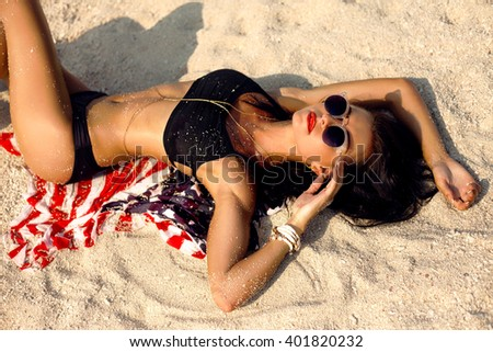Glamorous tanned Model in fashionable Swimsuit and stylish Accessories at the beach,American flag.California beach,Los angeles west coast.tropical beach, sexy tanned slim body, wet skin.belly close up