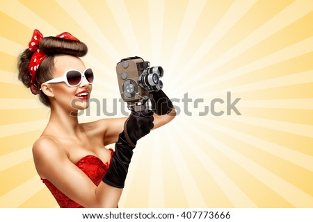 Glamorous vintage pin-up girl filming movie with an old retro cinema 8 mm camera, standing on colorful abstract cartoon style background. - stock photo