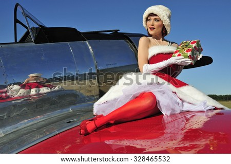 Glamorous woman dressed in a retro style Christmas dress and sitting on a wing of fighter plane - stock photo
