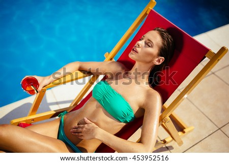 Glamorous woman enjoying her drink poolside and tanning - stock photo