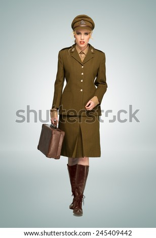 Glamorous woman in a stylish brown military uniform walking towards the camera carring an attache case, over grey - stock photo