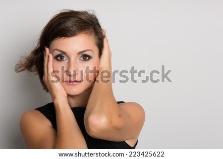 Glamorous woman in black on a gray wall. Woman 36 years old. - stock photo