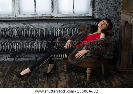 Glamorous woman in fur coat relaxing in a vintage room - stock photo