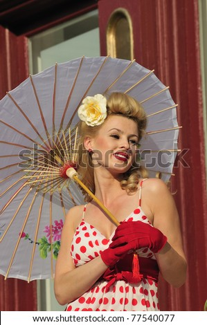 glamorous woman in 1940s fashion standing outside with an umbrella - stock photo