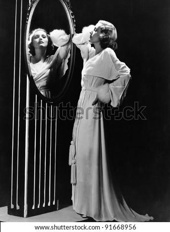 Glamorous woman looking in mirror - stock photo