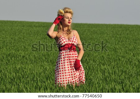 glamorous 1940 woman standing in a green field - stock photo
