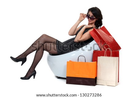 Glamorous woman surrounded by store bags - stock photo