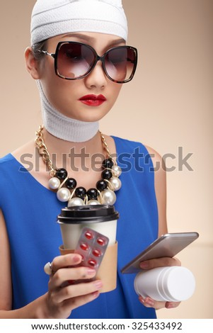 Glamorous woman with coffee and tables checking her phone after plastic surgery - stock photo