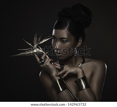 Glamorous woman with golden jewelry posing topless in front of a black background.