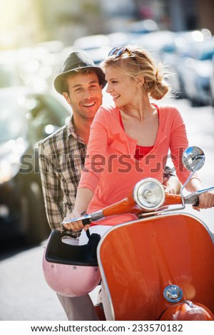 glamorous  young couple riding  a vintage scooter in the street, man wears a hat and woman has a topknot, sunglasses and a pink helmet - stock photo