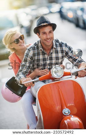 glamorous  young couple riding  a vintage scooter in the street, man wears a hat and woman has a topknot, sunglasses and a pink helmet