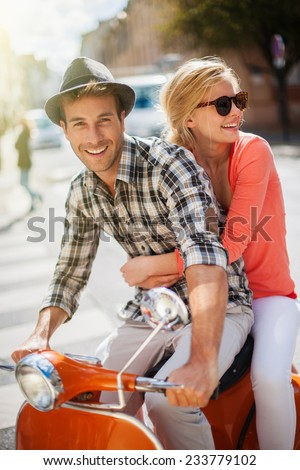 glamorous  young couple riding  a vintage scooter in the street, man wears a hat and woman has a topknot and sunglasses - stock photo