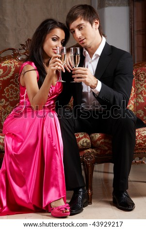 Glamorous young couple sitting on a sofa drinking champagne