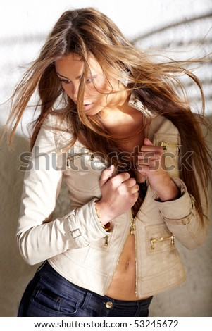 Glamorous young woman in a jacket near white wall - stock photo
