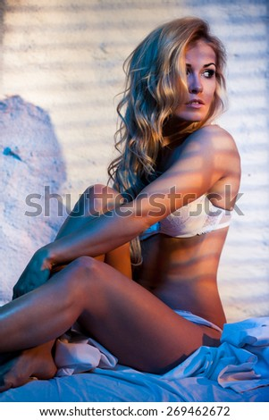 Glamorous young woman in sexy lingerie posing on a bed - stock photo