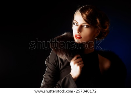 Glamorous young woman with evening make-up over dark background. Luxury. Beauty, fashion. Make-up.