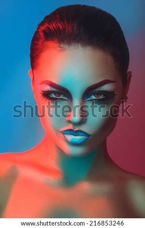 Glamour adult brunette with make up in red and blue lights in studio