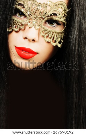 Glamour brunette woman in golden carnival mask - stock photo