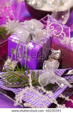 glamour christmas table decoration in purple color with gift box on glass plate - stock photo