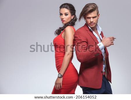 glamour couple looking away from the camera in studio, man smoking cigar - stock photo