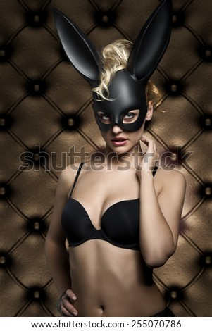glamour easter shoot of very sexy blonde female with curly hair-style and black lingerie, wearing stylish creative dark bunny mask on the face and looking in camera  - stock photo