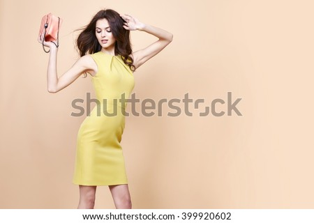 Glamour fashion woman long brunette curly hair natural evening makeup wear sexy short stylish yellow cotton dress from new catalog spring summer collection accessory handbag jewelry body shape care. - stock photo