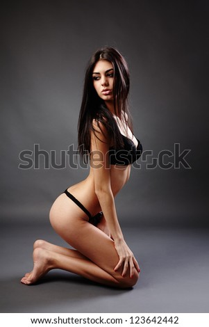 Glamour full length studio portrait of a young caucasian brunette woman on gray background - stock photo