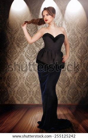 Glamour girl in an evening black dress in the interior