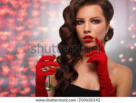 Glamour girl in red gloves holding a glass of champagne. drinking champagne. Beauty woman with perfect fashion makeup.congratulations on Valentine's Day