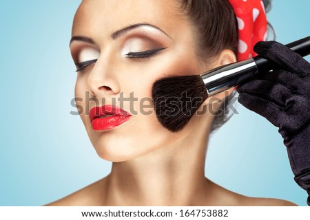 Glamour girl with fashion makeup painting her cheek with brush. - stock photo