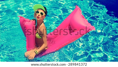Glamour Girl with inflatable mattress in the Pool.  Hot Summer party - stock photo