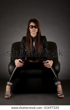 glamour girl with sunglasses sitting in  leather  chair on white