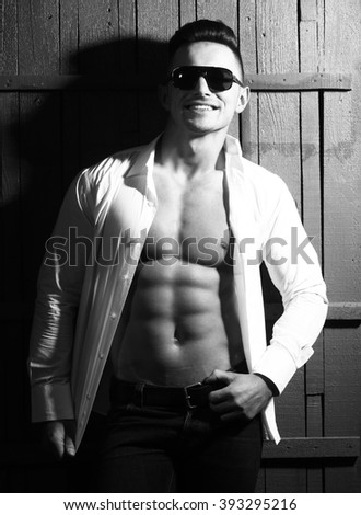 Glamour gorgeous happy smiling sexy young guy man with athletic muscular torso in trendy sunglasses dressd in unbutton shirt and dark trousers leaning on wooden wall black and white studio, vertical - stock photo