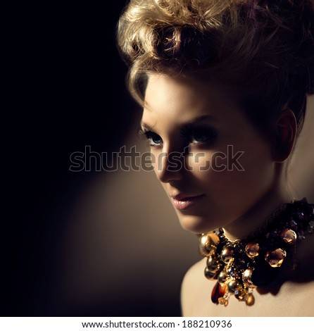 Glamour lady portrait. Beautiful model girl with perfect fashion makeup and hairstyle. Trendy accessories. Jewellery. Jewelry. Hairdo. Over Dark Background - stock photo