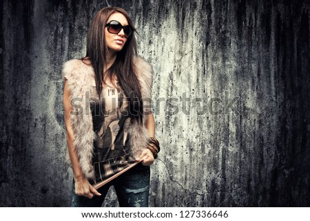 Glamour portrait of a beautiful young woman over concrete wall. - stock photo