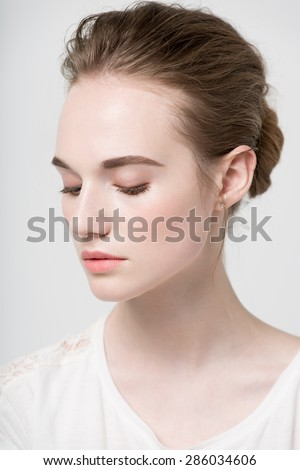 Glamour portrait of beautiful woman model with fresh daily makeup and funny wavy hairstyle. Fashion shiny highlighter on skin, sexy gloss lips make-up and natural eyebrows. gray background - stock photo