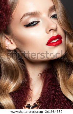 Glamour portrait of beautiful woman model with red lips and long blond hair in luxury fur coat color marsala