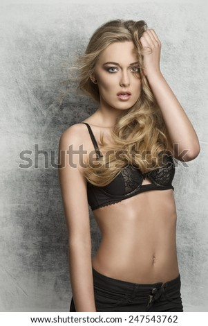 glamour portrait of sexy blonde lady with long hair black pants, stylish make-up and charming expression. Looking in camera  - stock photo