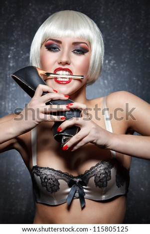 glamour portrait of sexy young woman with bright makeup in bra biting gold heel of shoe against dark background