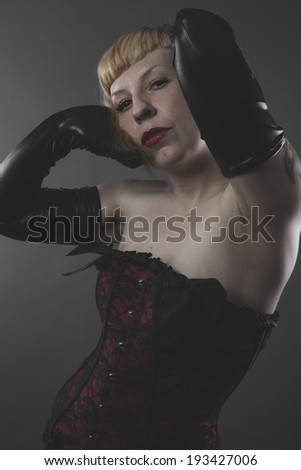 Glamour, sensual blond in red corset on gray background