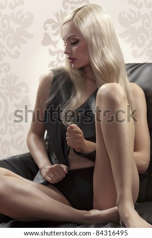 glamour shot of a blonde beauty sitting on a sofa wearing a black leather vest and panties - stock photo