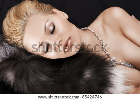 glamour shot of a sleeping blonde girl with an up-do laying on fur - stock photo