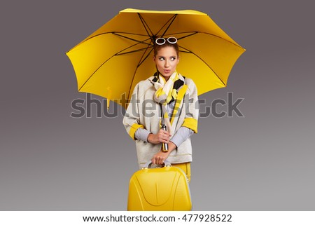 Glamour woman with yellow umbrella and suitcase. Travel concept