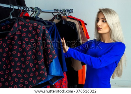 Glamour young blonde lady in clothing store. Beautiful young lady with a lot of clothes. Shopping concept. - stock photo