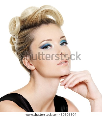 Glamour young woman with blue eye make-up and curly hairstyle on white background - stock photo