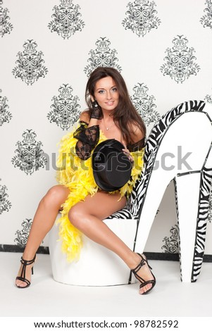 Glamoured portrait of fancy cabare dancer sits on high heel shoe - stock photo