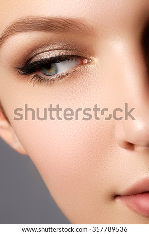 Glamourous closeup female portrait. Fashion evening elegance eyeliner makeup on model eyes. Cosmetics and make-up. Close-up portrait of young beautiful girl with cat eye make-up - stock photo